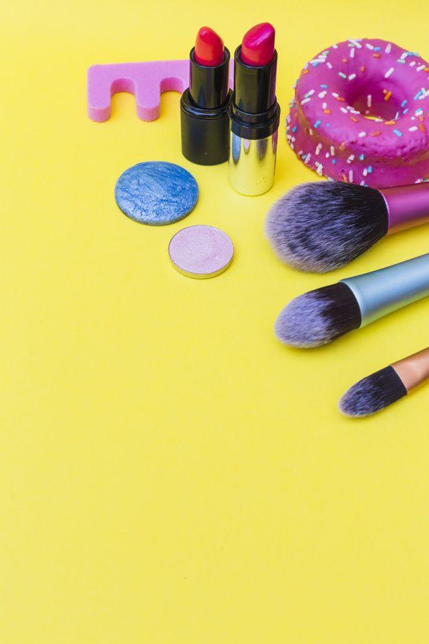 Rosquilla; brocha de maquillaje; lápiz labial; y sombras de ojos sobre fondo amarillo Foto gratis