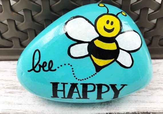 Spread happiness and encouragement! This cute hand-painted rock says Bee Happy and features a yellow and black bumblebee. The background is sky blue. It measures around 3.5 inches in length (size and shape will vary from stone to stone). This stone is painted with acrylics and sealed