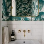 Small powder room with graphic wallpaper and subway tile. #remodelista #powderroom #bathroom #wallpaper