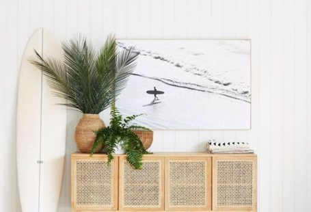 Beautiful beachy vibe with a cane console table in light wood, vertical white shiplap, large wall art, plants, and a surfboard! #entrywaydecor #foyerdecor #modern #coastal