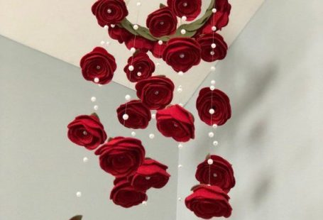 """Handmade. Shown in Red felt roses baby nursery mobile Pearl accents, fishing wire creates a beautiful illusion. 10"""" overall circumference . Approx. 40 roses - 20 on the ring, 20 hanging, nearly 100 pearls. 36"""" length. Ivory ribbon. All my mobiles are 100% customizable to your liking. I also offer in"""