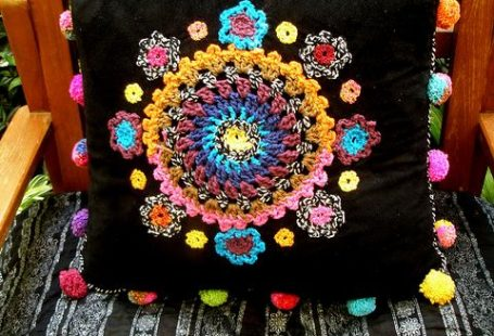 crocheted embellishments on cushion cover - pom-poms too!