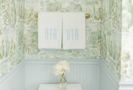 Bathroom with blue wainscoting and green scenic Sanderson wallpaper and monogrammed Weezie towels by Tori Alexander of Alexander Interiors in Nashville.